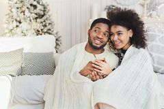 Couple relaxing with glass of warm wine on winter evening. Cozy winter evening. African-american men and women embracing, sitting under warm blanket and sharing stock photos