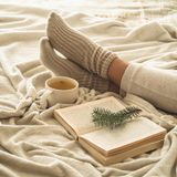 Cozy winter evening , warm woolen socks. Woman is lying feet up on white shaggy blanket and reading book. Cozy leisure scene. Text in book is unreadable. Woman royalty free stock image