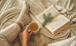 Cozy winter evening , warm woolen socks. Woman is lying feet up on white shaggy blanket and reading book. Cozy leisure scene. Text in book is unreadable. Woman stock image