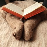 Cozy Winter fall autumn lifestyle: woman in warm cute bear socks with book. Retro toning, beige monochrome, hipster still life. Cozy Winter fall autumn stock image