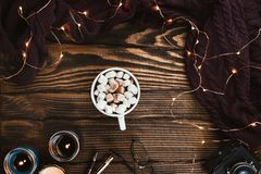Cozy winter flatlay arrangement with Christmas lights, vegan cocoa, glasses, knitted sweater and candles. On dark wooden background royalty free stock photos
