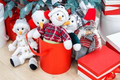 Cozy winter holidays background. Funny toy snowmen and presents waiting for christmas under decorated fir tree. Joyful royalty free stock image