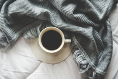 Cozy winter home background, cup of hot coffee with marshmallow, warm knitted sweater on white bed background, vintage tone.
