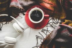 Cozy winter home background, cup of hot coffee with marshmallow, warm knitted sweater on white bed. Background, vintage tone.  Lifestyle concept Royalty Free Stock Images