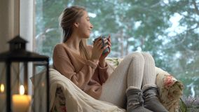 Young happy woman enjoy of cup of hot coffee sitting home by the big window with winter snow tree background stock video footage