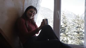 Cozy winter lifestyle. Young happy woman drinking cup of coffee wearing knitted sweater sitting home by the big window stock video