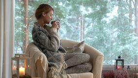 Cozy winter lifestyle. Young happy woman drinking cup of coffee wearing knitted sweater sitting home by the big window stock footage