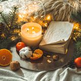 Book and Tangerines in a winter composition, Christmas trees, candles, cones, cotton, cinnamon. Symbol of New Year and Christmas stock images