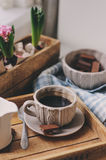 Cozy winter morning at home. Coffee, milk and chocolate on wooden tray. Huacinth flowers on background. Warm mood Stock Photos