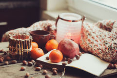 Cozy winter morning at home with fruits, nuts and candles, selective focus Stock Images
