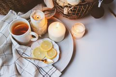 Cozy winter morning at home. Hot tea with lemon, candles, knitted sweaters in basket and modern metallic interior details. Still l Royalty Free Stock Images