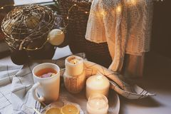 Cozy winter morning at home. Hot tea with lemon, candles, knitted sweaters in basket and modern metallic interior details. Still l Stock Images