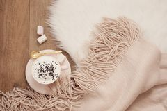 Cozy Winter Mornings. Cappuccino and a warm scarf on a white fur carpet on the floor. Cozy Winter Mornings. Cappuccino and a warm scarf on a white carpet on the stock images
