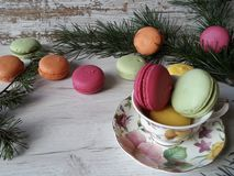 Cozy winter scene with colorful macaroons. Macaroons in pretty colors on a white wooden background Royalty Free Stock Photos