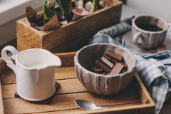 Cozy winter or spring morning at home. Coffee, milk and chocolate on wooden tray. Hyacinth flowers on background Royalty Free Stock Photo