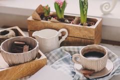 Cozy winter or spring morning at home. Coffee, milk and chocolate on wooden tray. Hyacinth flowers on background. Warm mood Stock Image