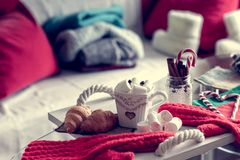 Cozy winter still life, consist of, cup of coffee, marshmallow, croissants, striped lollipop. On the foreground and fur shoes with sweaters in the home interior stock images