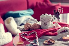 Cozy winter still life, consist of, cup of coffee, marshmallow, croissants, striped lollipop. On the foreground and fur shoes with sweaters in the home interior stock photography