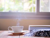 A cup of hot coffee with smoke and a book with warm on wooden table, window background. royalty free stock photos
