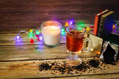 Cozy winter still life: cup of hot tea and books, candle on wooden background and blurred garland lights. Christmas concept royalty free stock photos