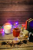 Cozy winter still life: cup of hot tea and books, candle on wooden background and blurred garland lights. Christmas concept royalty free stock images