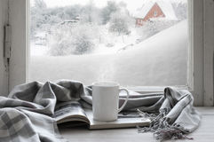Cozy winter still life. Mug of hot coffee and opened book with warm plaid on vintage windowsill of cottage against snow landscape with snowdrift from outside Royalty Free Stock Images