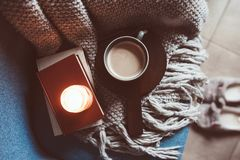 Cozy winter weekend at home. Morning with coffee or cocoa, books, warm knitted blanket and nordic style chair. Hygge concept. Cozy winter weekend at home Royalty Free Stock Image