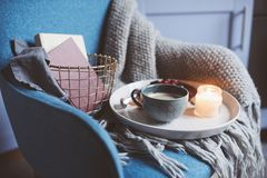 Cozy winter weekend at home. Morning with coffee or cocoa, books, warm knitted blanket and nordic style chair. Hygge concept. Cozy winter weekend at home