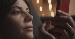 Cozy woman using her cellphone on the couch at night. Shot in 4K RAW on a cinema camera. Anamorphic bokeh stock footage