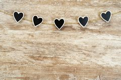 Cozy wooden background, with 5 black hearts fastened between them with a hemp rope, love concept, for Valentine`s Day,. Mother`s Day, Father`s Day, Christmas royalty free stock photography