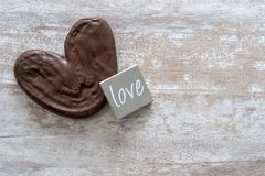Cozy wooden background, with a chocolate palm tree, a piece of wood with the word love written, love concept, for Valentine`s Day. Mother`s Day, Father`s Day stock photography