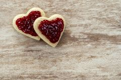 Cozy wooden background, with 2 heart-shaped sandwich bread in a corner, with strawberry jam, love concept, for Valentine`s Day,. Mother`s Day, Father`s Day stock images