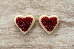 Cozy wooden background, with 2 heart-shaped sandwich bread with strawberry jam in the center, love concept, for Valentine`s Day, royalty free stock photo