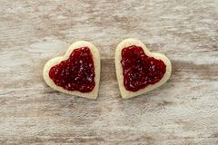 Cozy wooden background, with 2 heart-shaped sandwich bread with strawberry jam in the center, love concept, for Valentine`s Day,. Mother`s Day, Father`s Day royalty free stock image