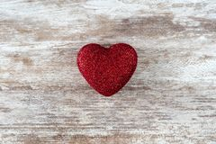 Cozy wooden background, with a red heart with glitter in the center, love concept, for Valentine`s Day, Mother`s Day, Father`s stock photography