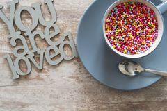 Cozy wooden background, with the text you are loved, with a blue cup with colored balls inside, concept, for Valentine`s Day,. Mother`s Day, Father`s Day royalty free stock photography