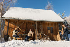 Cozy wooden cottage winter snow people outside stock photo