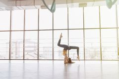 Young attractive girl doing fitness exercises with yoga on the floor against the background of panoramic windows royalty free stock images