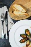 Cozze al forno in salsa al pomodoro con coriandolo e parmigiano su un piatto bianco immagini stock