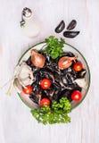 Cozze crude in ciotola con acqua, le spezie e l'olio Immagine Stock