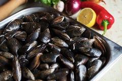Cozze fresche con gli ingredienti per la cottura sul fondo rustico, vista superiore, confine Concetto dei frutti di mare Immagini Stock