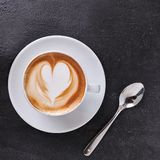 Cp of hot cappuccino in square format. Top view of cup of creamy cappuccino with the shape of a heart, on dark stone background. Square format banner stock images