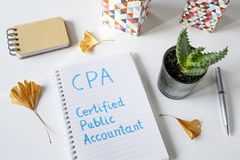 CPA Certified Public Accountant written in notebook. On white table Stock Photo