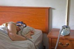 cpap设备休眠的妇女 免版税库存图片