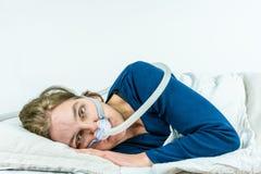 CPAP behandling för sömnapnea Kvinnan som lägger på hennes sida med ögon, öppnar Arkivbilder