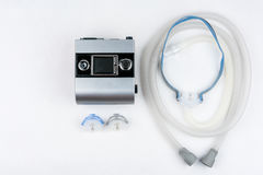 CPAP machine with hose and mask for nose. Treatment for people with sleep apnea. Stock Photo