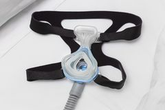 CPAP mask, headgear strap, and air hose on white bed Royalty Free Stock Image