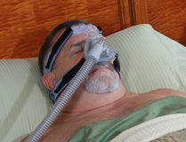 CPAP Mask On Adult Face. A man sleeps peacefully with a CPAP mask Royalty Free Stock Photo