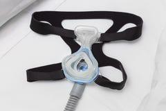 CPAP maskują, kłobuk patka i lotniczy wąż elastyczny na białym łóżku, obraz royalty free