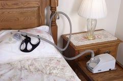 CPAP Schlafapnea-Maschine, die auf Bett im Schlafzimmer liegt Lizenzfreie Stockfotos